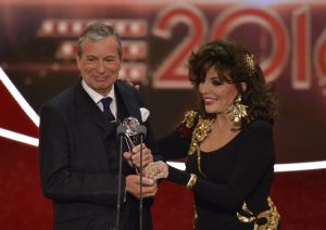 Embargoed: for publication from 22.30 on Saturday 28th May 2016 From ITV Studios THE BRITISH SOAP AWARDS 2016 Sunday 29th May w2016 on ITV Pictured: Best Soap Winner John Middleton Emmerdale accepts the award from Joan Collins The British Soap Awards returns to celebrate another mammoth year in soap opera, looking back on twelve months of murder, mystery, make ups, break ups, trials, tribulations and tears. An incredible year in which Kathy Beale returned from the dead on EastEnders, Callum Logan met his maker on Coronation Street, the glove handed killer continued her reign in Hollyoaks, the Summer fete in Emmerdale changed lives forever and Doctors celebrated their 3000th episode with an hour long special. The 18th annual awards will take place later this month in London at the Hackney Empire Theatre. They will honour the nationÕs biggest and best-loved TV shows, as well as the stars that have appeared in this yearÕs most talked about storylines. The five biggest soaps - Coronation Street, Doctors, EastEnders, Emmerdale and Hollyoaks - will be battling it out to win recognition for their work over the past year. Stars from all five soaps will be hitting the red carpet for the most star-studded event in the soap calendar. Hosted by Phillip Schofield, the awards will be presented by an array of well-known faces from across the TV and showbiz world. The British Soap Awards recognise outstanding achievement in the countryÕs most popular television genre. There are 15 awards voted for either by both the public and a panel of expert judges. (c) ITV Photographer: Kieron McCarron